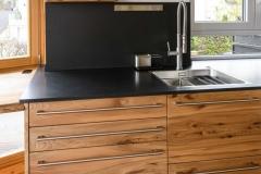 Massivholzküche mit bündig eingelassener Spüle in Granitplatte