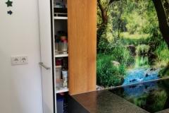tiefer Apotherschrank hinter dem Küchenblock; raumhoch; schwarz durchgefärbter MDF-Schichtstoff